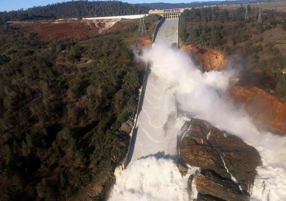 Foto: La presa de Oroville desaloja agua por su compuerta principal y por su aliviadero primario. El penacho de agua que aparece se debe al agujero en el túnel de hormigón.