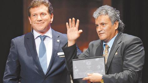 El exfutbolista Marco Antonio Etcheverry recibe del presidente de CONMEBOL, Alejandro Domínguez, la plaqueta de condecoración. Foto: AFP