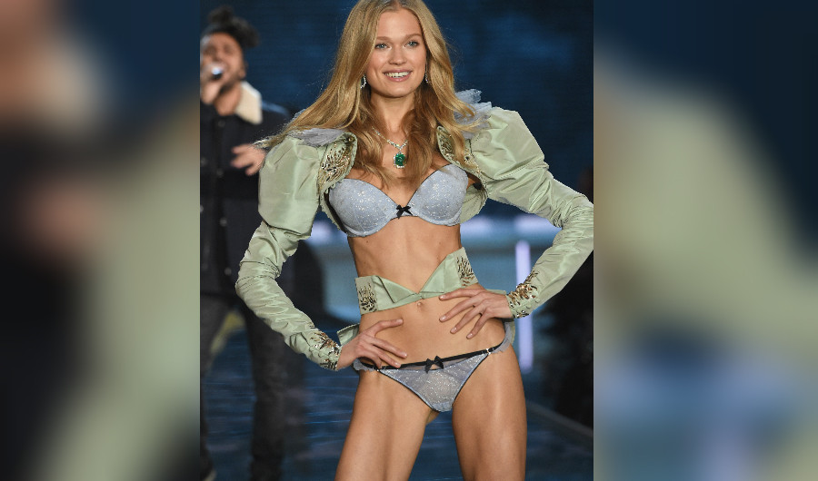 La rusa Vita Sidorkina desfila en pasarela durante el show de Victoria Secret  mientras al fonde se ve al canante The Weekend.  (Crédito: Dimitrios Kambouris/Getty Images)