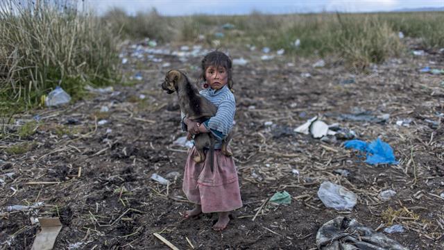 Melinda Quispe camina sobre la basura derramada a orillas del lago Titicaca, con su perro en brazos , en Kapi Cruz Grande, en la región de Puno en Perú
