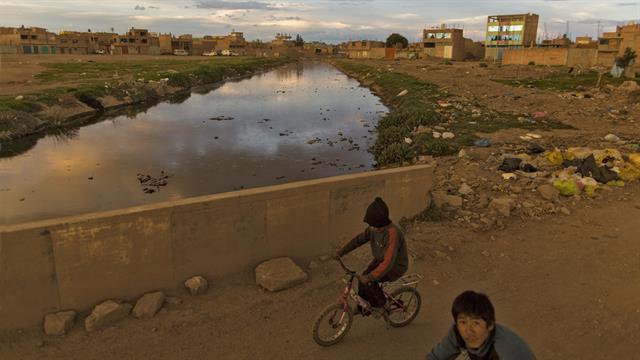 Niños en bicicleta sobre un puente del río Torococha cerca de una planta de tratamiento de residuos municipales con agua que desemboca en el Lago Titicaca, en Juliaca, en la región de Puno, Perú.