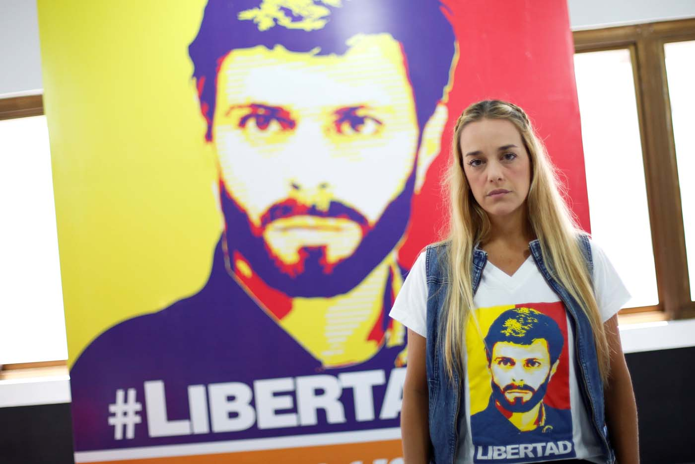 Lilian Tintori, wife of jailed Venezuelan opposition leader Leopoldo Lopez, poses for a picture in front of a poster depicting her husband at the office of the party Popular Will (Voluntad Popular) in Caracas, Venezuela January 18, 2017. Picture taken January 18, 2017. REUTERS/Carlos Garcia Rawlins