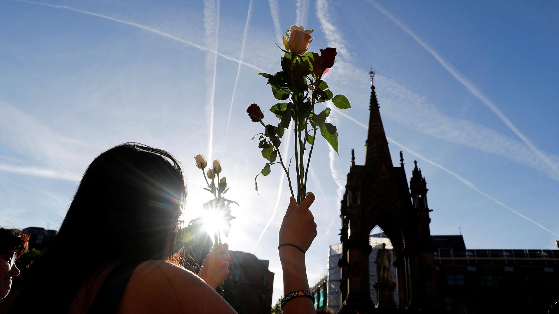 Una mujer sostiene un ramos de flores en medio de la vigilia (REUTERS)