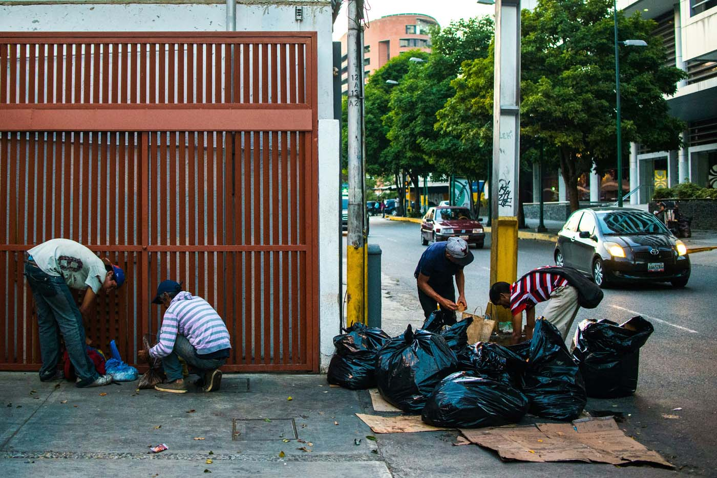 People scavenge for food in the streets of Caracas on February 22, 2017. Venezuelan President Nicolas Maduro is resisting opposition efforts to hold a vote on removing him from office. The opposition blames him for an economic crisis that has caused food shortages. / AFP PHOTO / Federico PARRA