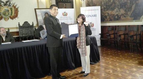 Canciller Huanacuni entrega el certificado de nacionalización a una ciudadana refugiada en Bolivia