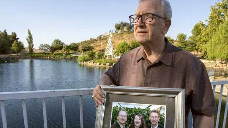 Frank Kerrigan y una foto de sus tres hijos, al vivir la confusa experiencia de enterrar a alguien que no era quien creía (AP)