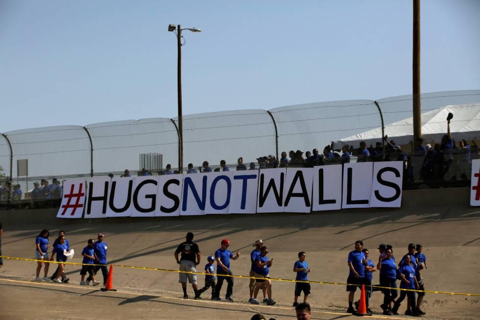 """Un encuentro de familiares en la frontera entre Ciudad Juárez y El Paso, el pasado sábado, bajo una pancarta que reza: """"Abrazos, no muros"""""""