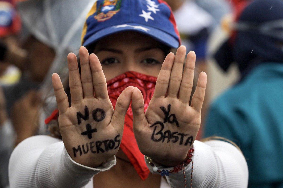 """CAR32. CARACAS (VENEZUELA), 24/06/2017.- Una mujer muestra un mensaje escrito en las palmas de sus manos durante una manifestación denominada """"Venezuela le da un mensaje a la FAN (Fuerza Armada)"""" hoy, sábado 24 de junio de 2017, en Caracas (Venezuela). La oposición venezolana se moviliza hoy hasta las bases militares en Caracas y varios estados del país, mientras el chavismo marcha para conmemorar los 196 años de la Batalla de Carabobo, una acción militar decisiva en la independencia del país caribeño, y por el Día del Ejército Bolivariano. EFE/Miguel Gutiérrez"""