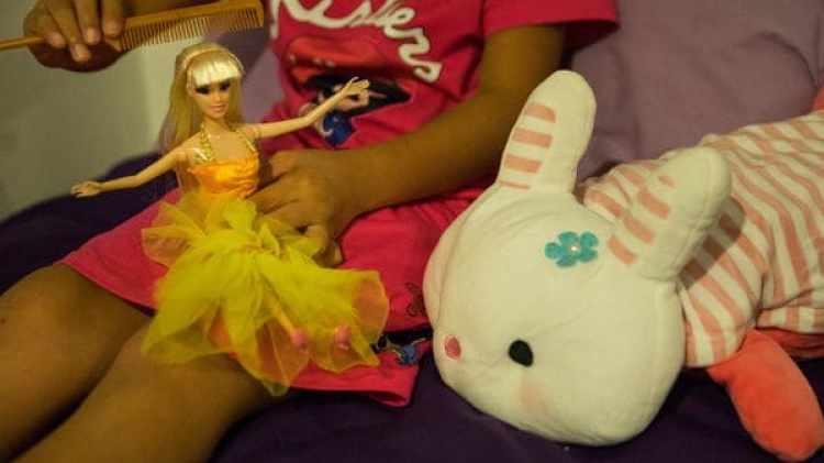 Una niña de 8 años peina el cabello de una muñeca que recibió como regalo al llegar a Nakhon Phanom, en Tailandia. (Paula Bronstein/The Washington Post)