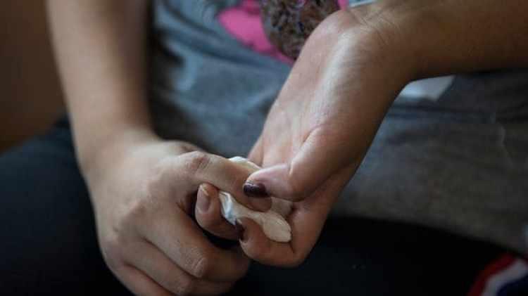 Una desertora norcoreana sujeta un pañuelo mientras llora y cuenta su historia. (Paula Bronstein/The Washington Post)