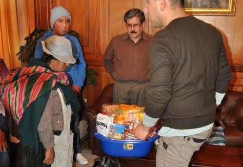 Autoridades universitaria hacen entrega de un canastón a la señora María