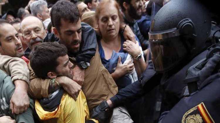 Policía antidisturbios de enfrenta a los catalanes que buscaban votar (EFE)