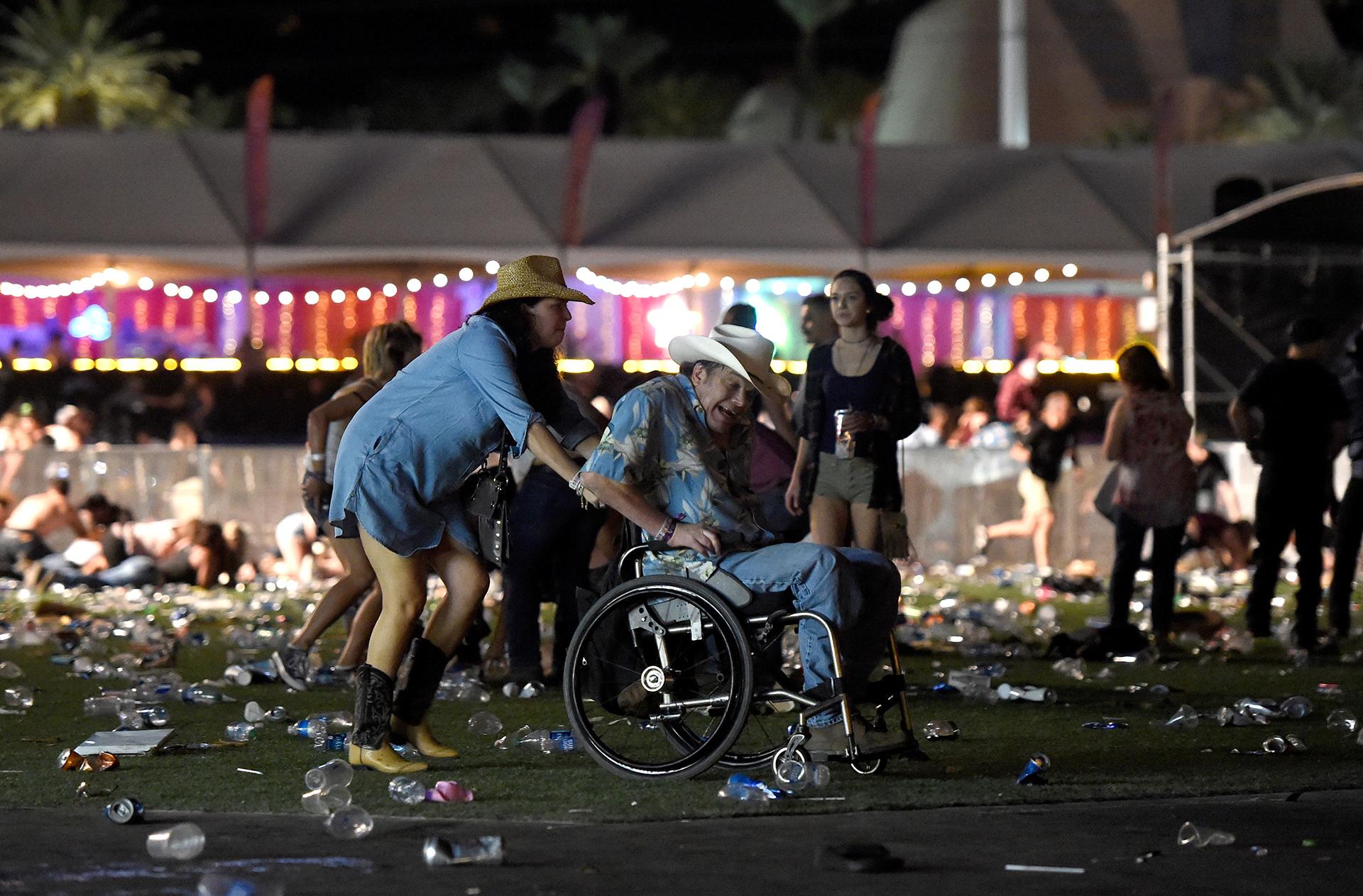 Un hombre en silla de ruedas es ayudado a escapar después de los disparos.