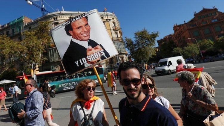 Un asistente a la marcha porta un meme como afiche (Reuters)