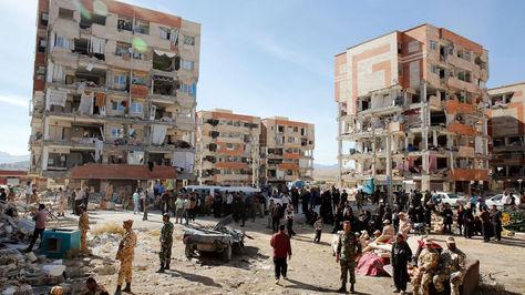 Víctimas del fuerte terremoto de 7,3 grados en la escala de Richter que asoló anoche la provincia de Kermanshah permanecen junto a edificios dañados en la ciudad de Pole-Zahab (Irán).