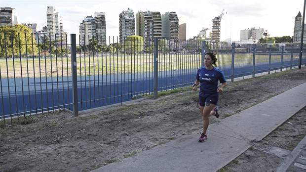 Una deportista amateur corre por el perímetro del Parque Chacabuco mientras aguarda la pista sintética