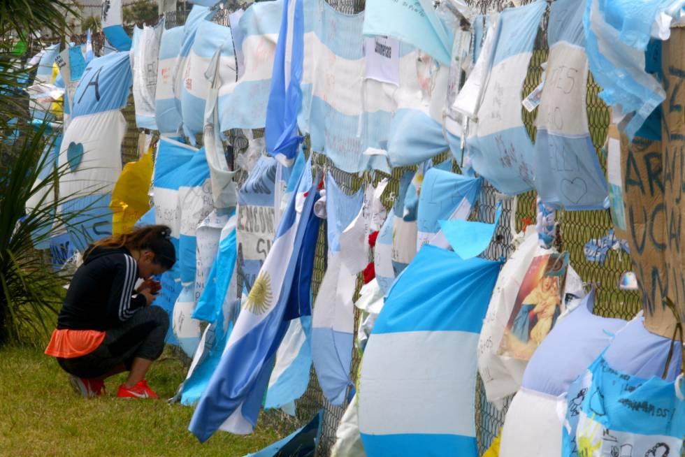 Una mujer se arrodilla ante las banderas que homenajean a los 44 tripulantes del Ara San Juan, en la base naval de Mar del Plata.