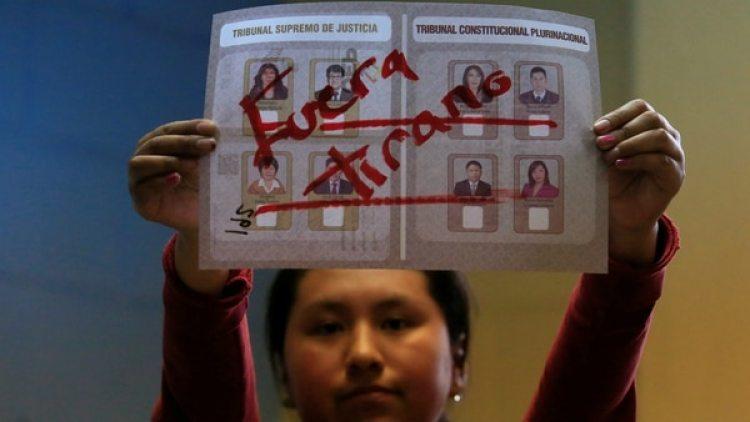 Una mujer sostiene el el papel del voto alterado que declara el voto como nulo. (Reuters)