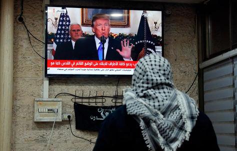 Un palestino ve una conferencia de prensa de Donald Trump. Foto: AFP