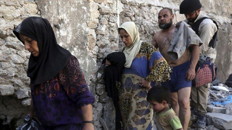 Un grupo de civiles abanadona su escondite tras el fin de la batalla. El hombre está en ropa interior para demostrar que no es un combatiente del ISIS camuflado (EFE)