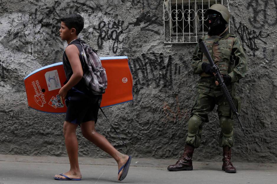 Un joven con una tabla de body-board pasa delante de un soldado desplegado en la favela de Rocinha durante una operación antidroga, en septiembre de 2017. (Reuters)