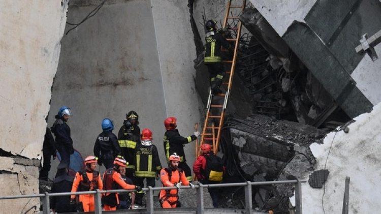 Miembros de los servicios de emergencia buscan entre los escombros tras derrumbarse una sección del viaducto Morandi en Génova (EFE)