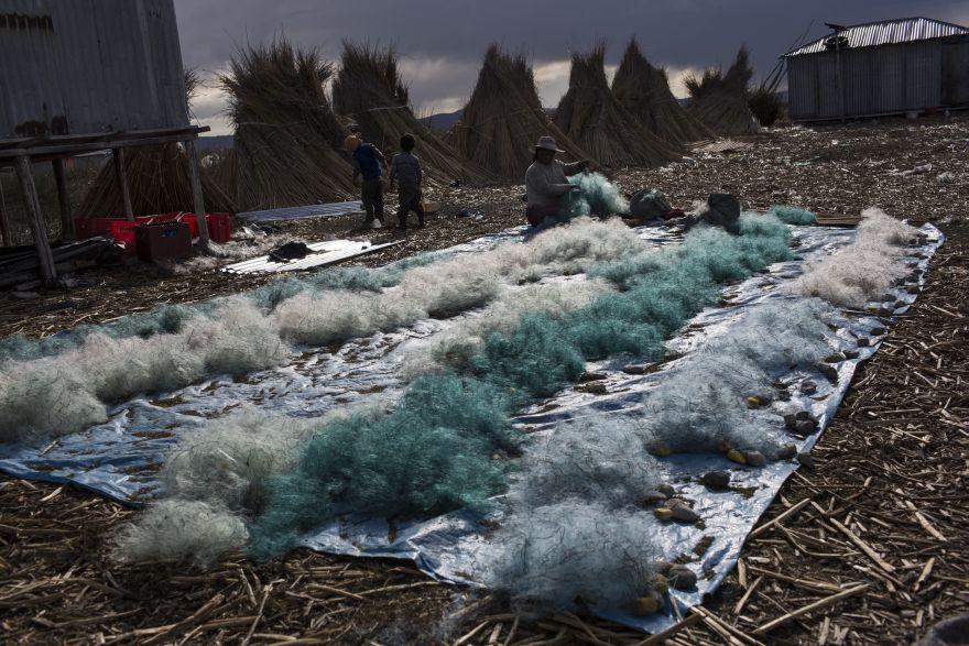 Naty Lugano Quispe limpia las redes de pesca en Kapi Cruz Grande, una aldea en la orilla del lago Titicaca. Un estudio de 2014 sugirió que los funcionarios limiten el consumo de pescado, pero los habitantes de la zona dijeron que no recibieron información acerca de dicho estudio o que no fueron advertidos de que podrían estar consumiendo pescado contaminado con mercurio, cadmio, zinc y cobre a niveles superiores a los recomendados para el consumo humano. (Foto: AP/Rodrigo Abd)