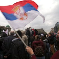 epa05895473 Protestants hold a Serbian flag in front of Serbian parliament building in Belgrade, Serbia, 07 April 2017. Several thousand people protested because of the results of presidential elections. Protesters are denouncing the 02 April presidential election victory of Aleksandar Vucic. EPA/KOCA SULEJMANOVIC