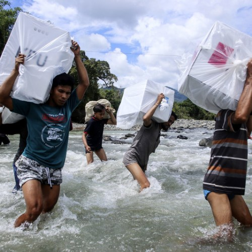 Photo Story – Indonesian election workers carrying ballot boxes to remote villages