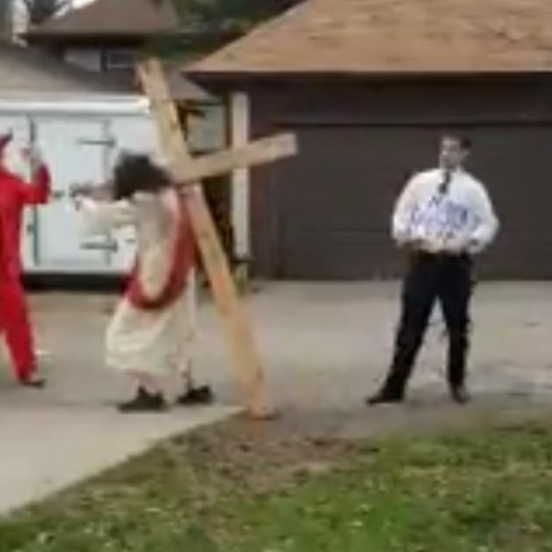 Homophobic protester dressed as Pete Buttigieg whips Jesus on the cross at political rally while 'devil' cheers him