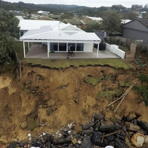 Australian houses on the brink of collapse as wild seas batter the coast