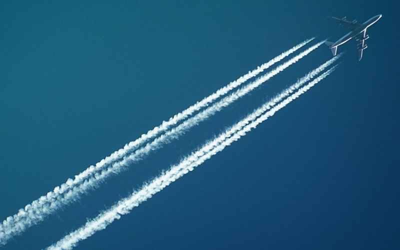white airplane with smoke under blue sky