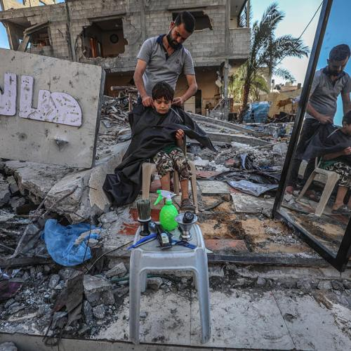 Photo Story – A Palestinian barber works amid the rubble of his destroyed shop