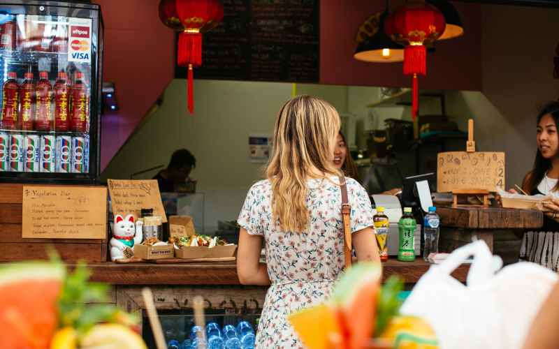 woman in floral dress standing in front of a snack bar with wooden counter