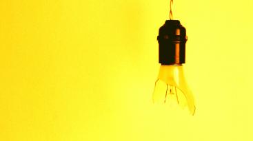 Brocken lightbulb with a yellow background.