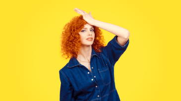 Woman patting her head in frustration in front of a yellow background.