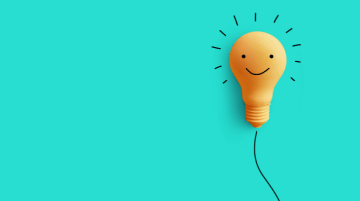 Orange lightbulb with a smiley face against a green background