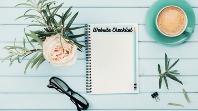 Notepad with title 'Website Checklist' on desk with coffee, glasses and flower.