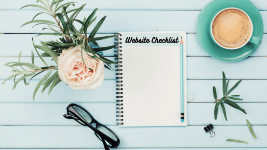 Notepad with title 'Website Checklist' on a desk with a pencil, cup of coffee, flower and glasses.