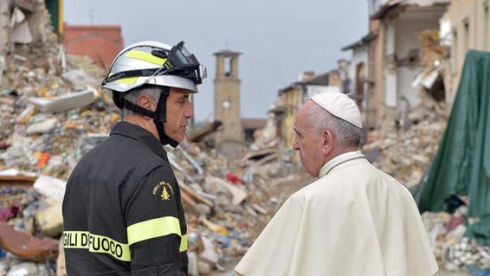 Pope Francis talks to a firefighter in the quake-struck town of Amatrice (AP)