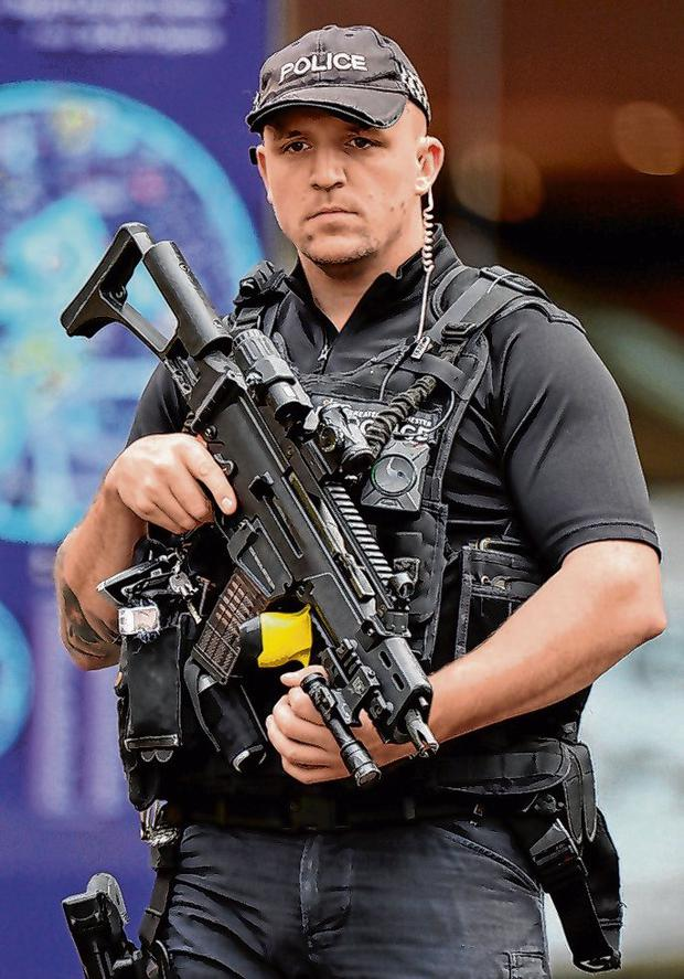 An armed officer stands guard. Photo: Peter Powell/Reuters