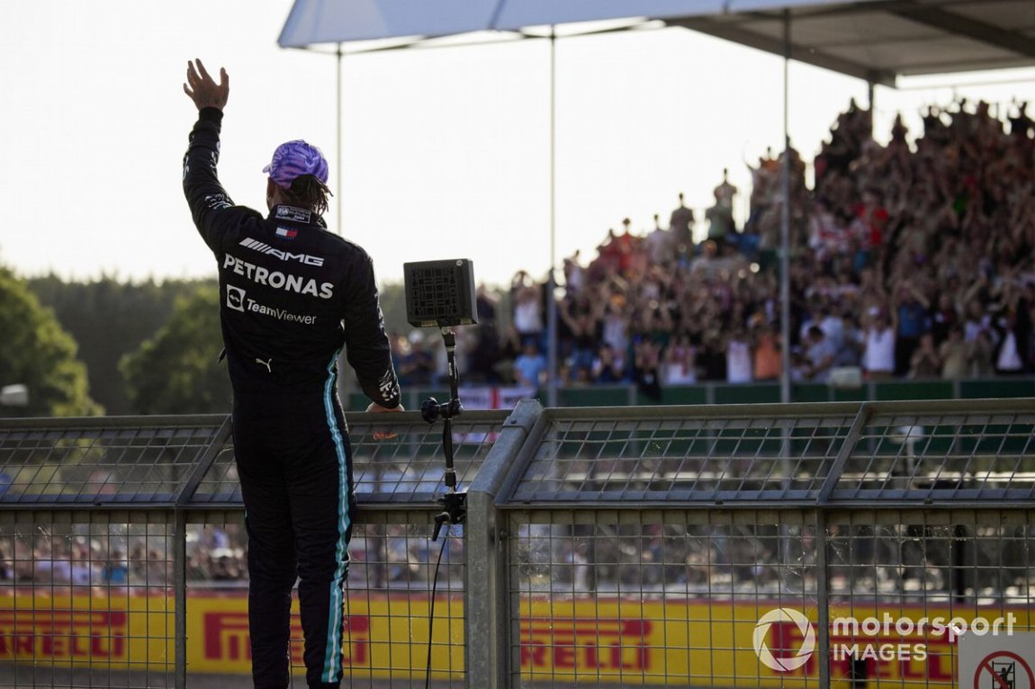 Lewis Hamilton, Mercedes, climbs the fence after securing pole