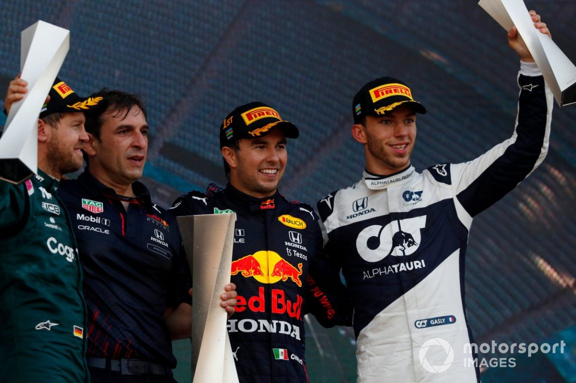Sebastian Vettel, Aston Martin, 2nd place, Red Bull trophy delegate, Sergio Perez, Red Bull Racing, 1st place, and Pierre Gasly, AlphaTauri, 3rd place, on the podium