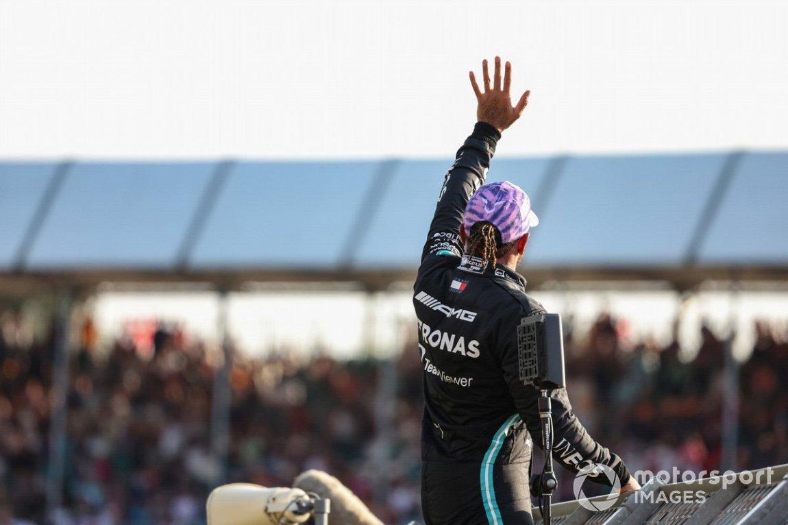 Pole man Lewis Hamilton, Mercedes, climbs the fence to greet fans