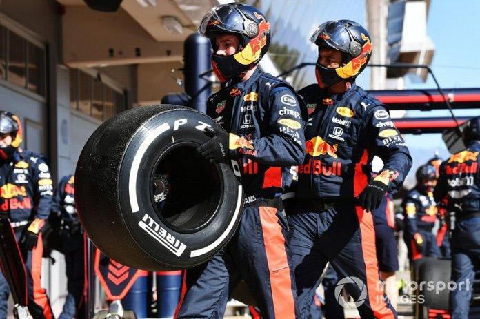 Los mecánicos de Red Bull llevan un neumático después de una parada en boxes