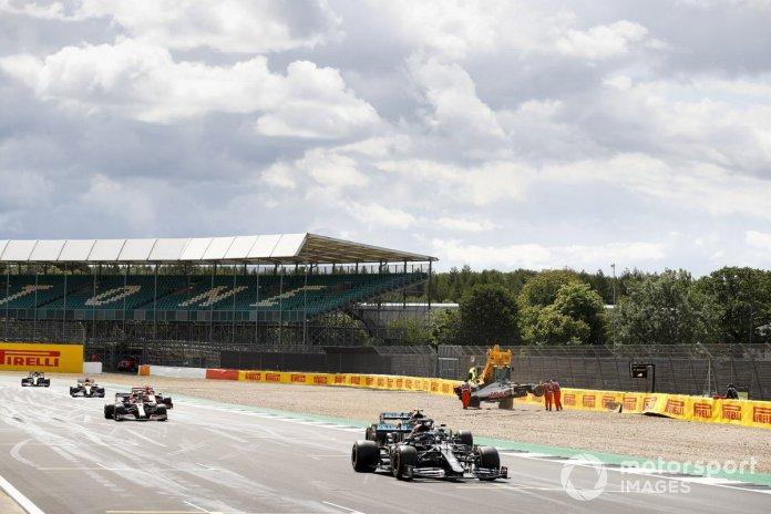 Lewis Hamilton, Mercedes F1 W11, Valtteri Bottas, Mercedes F1 W11, Max Verstappen, Red Bull Racing RB16, y el monoplaza chocado de Kevin Magnussen, Haas VF-20