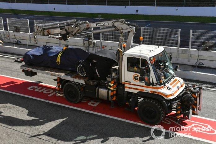 El monoplaza de Max Verstappen Red Bull Racing RB16 es devuelto a los boxes en la parte trasera de una grúa