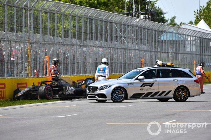 El coche médico y los oficiales atienden al coche dañado de Kevin Magnussen, Haas F1 Team VF-19