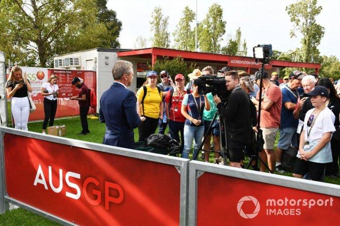 Un oficial habla a los medios mientras los fans escuchan