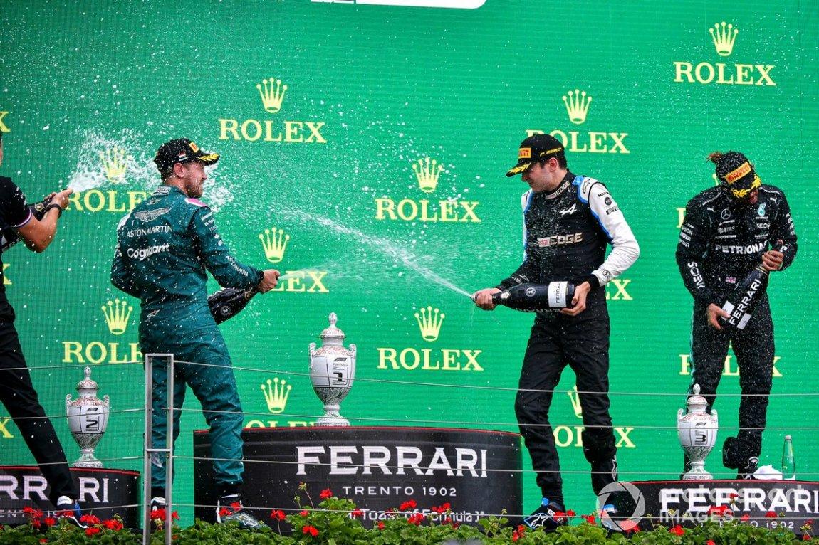 Sebastian Vettel, Aston Martin, second place, Esteban Ocon, Alpine F1, first place, and Lewis Hamilton, Mercedes, third place, sprinkle Champagne on the podium